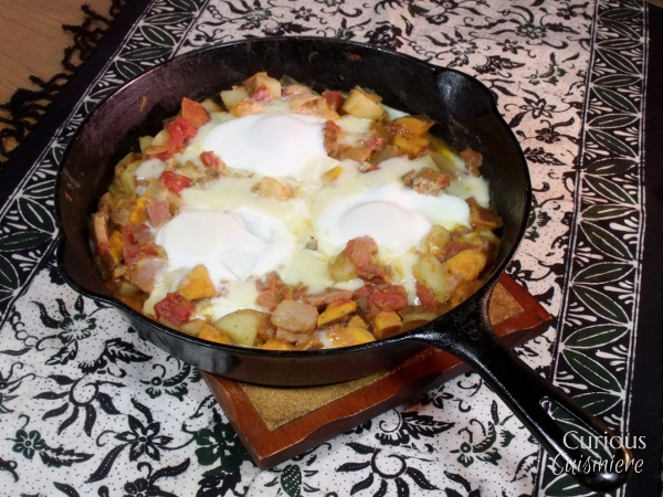 Explore the savory side of sweet potatoes with this Sweet Potato Hash Breakfast Skillet, made hearty with ham, tomatoes, eggs, and two kinds of potatoes. | Curious Cuisiniere