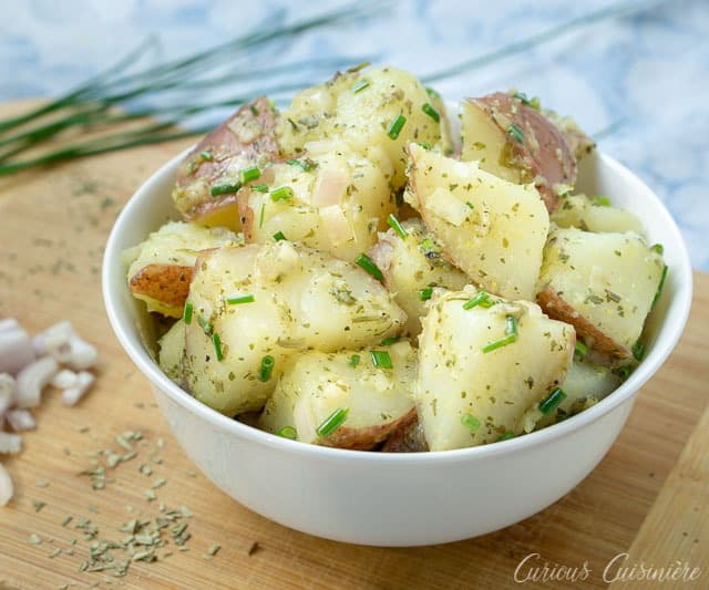 French Potato Salad is a welcoming blend of French herbs in a light red wine vinaigrette dressing. This potato salad recipe is perfect for a summer cookout! | www.CuriousCuisiniere.com