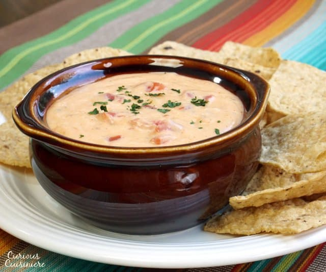 This Smoky Chili Con Queso Sauce makes for some mean cheese nachos, or if you prefer, just grab a bowl and start dipping anything you have on hand. Chips, bread, veggies: they're all better with a little cheese! | www.CuriousCuisiniere.com