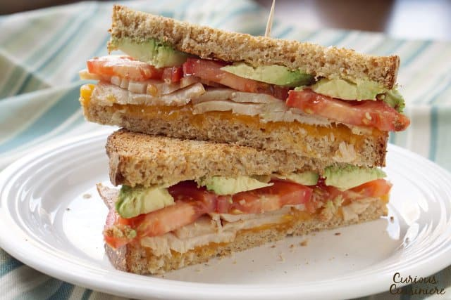 Smooth avocado pairs with juicy turkey, tomatoes, and the sharp cheddar cheese to make the perfect, warm and toasty Turkey Avocado Melt. | www.CuriousCuisiniere.com