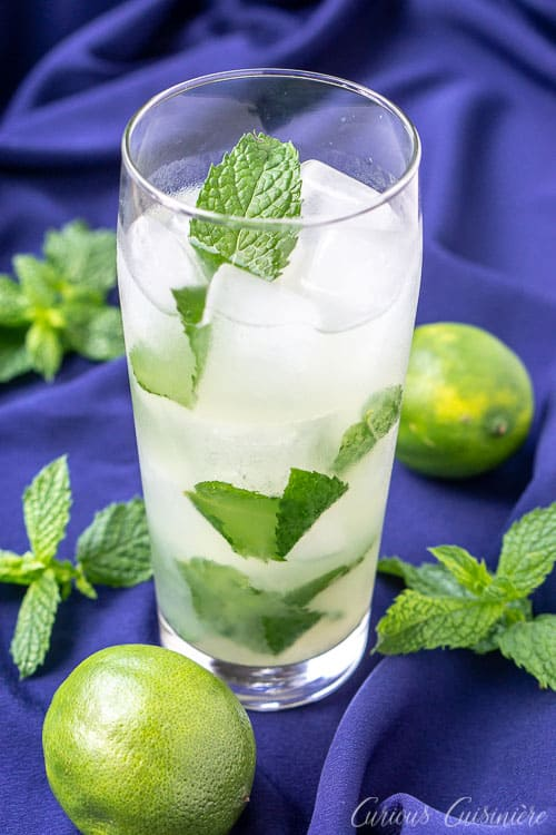 Cuban Mojito in a tall glass with a mint leaf on top. The classic Cuban Mojito cocktail is a sweet and citrusy beverage made with fresh mint and white rum. | www.CuriousCuisiniere.com
