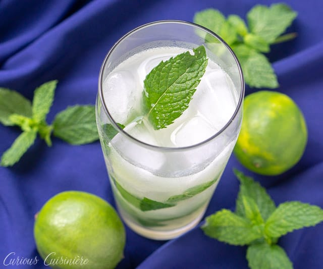 Cuban mojito beverage on a blue background with limes and fresh mint leaves. mint, lime and white rum. | www.CuriousCuisiniere.com