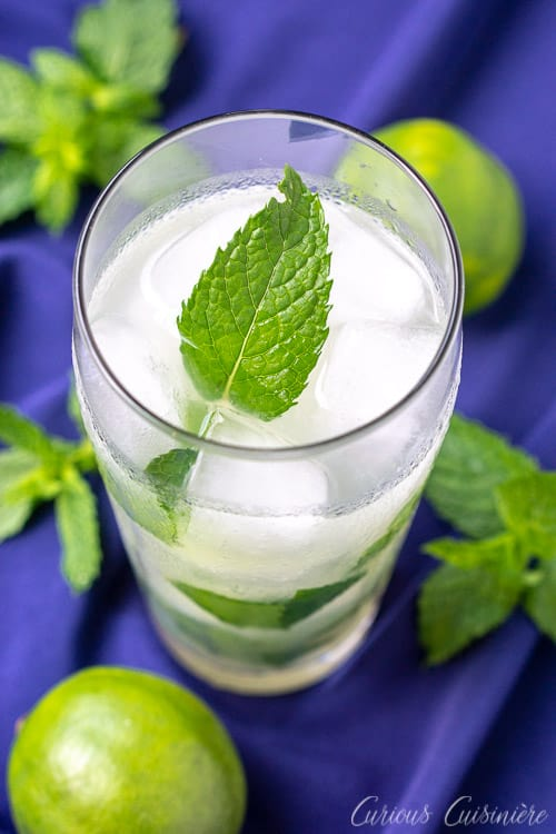 Vertical image of a Cuban mojito beverage on a blue background with limes and fresh mint leaves. mint, lime and white rum. The classic Cuban Mojito cocktail is a sweet and citrusy beverage made with fresh mint and white rum. | www.CuriousCuisiniere.com