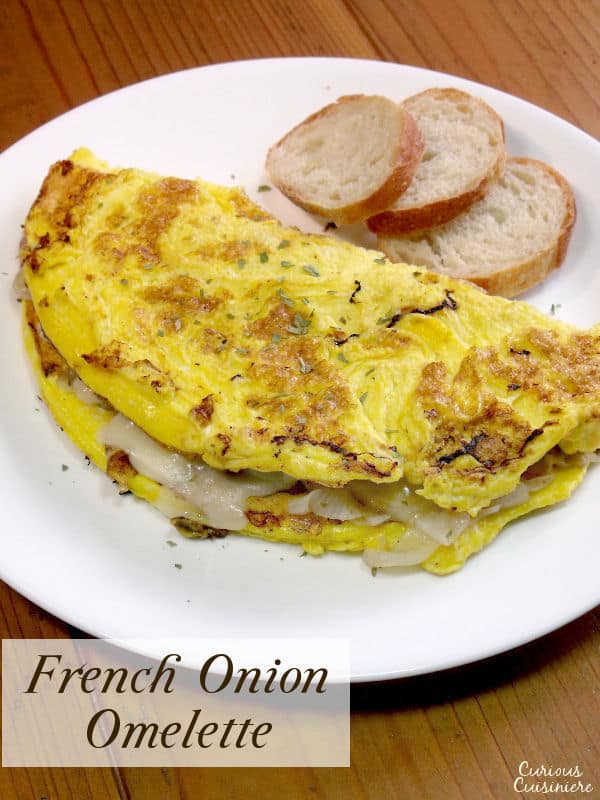 Fluffy eggs are filled with flavorful caramelized onions and sharp Swiss cheese in an omelette inspired by the flavors of French onion soup. | www.CuriousCuisiniere.com