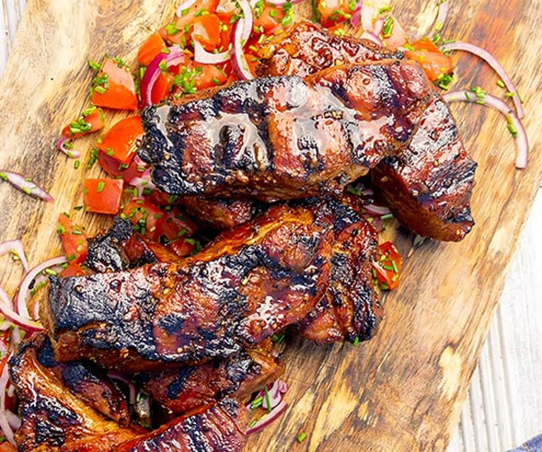 Country style rib marinade on pork ribs, stacked on a cutting board