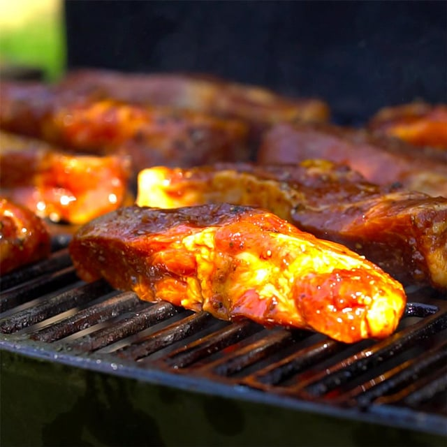 Grilling country style ribs with marinade, side shot