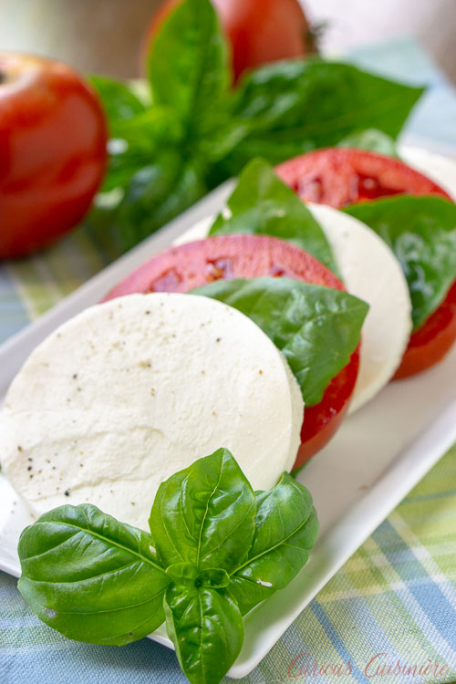A summer favorite Insalata Caprese (or Caprese Salad), with rounds of fresh mozzarella, ripe tomatoes, and garden basil. | www.CuriousCuisiniere.com