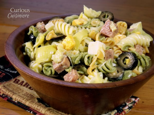 The classic flavors of an Italian Antipasto plate are tossed together to make this fun and flavorful Antipasto Pasta Salad with summer sausage, cheese, and olives. | Curious Cuisiniere