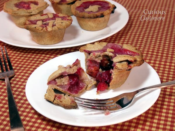 These hand-held Mini Cherry Pies with a whole wheat crust are bursting with juicy cherry goodness and are the perfect make ahead summer dessert. | Curious Cuisiniere