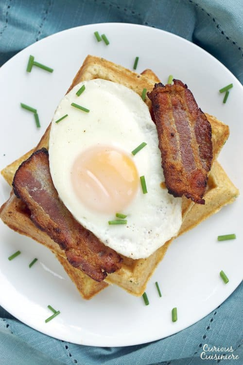 A stack of delicious, savory Cornmeal Waffles is the perfect breakfast or dinner, particularly with a fried egg and bacon! | www.CuriousCuisiniere.com