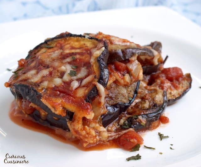 Parmigiana di Melanzane, or Eggplant Parmesan, is a simple but elegant Italian recipe. Our version of this vegetarian dish is lighter than many and includes a Fresh Herb Tomato Sauce that is perfect for summer! | www.CuriousCuisiniere.com