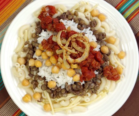 Often called the national dish of Egypt, Kushari is a hearty combination of flavors and textures all topped off with spicy tomato sauce and fried onions. | www.CuriousCuisiniere.com
