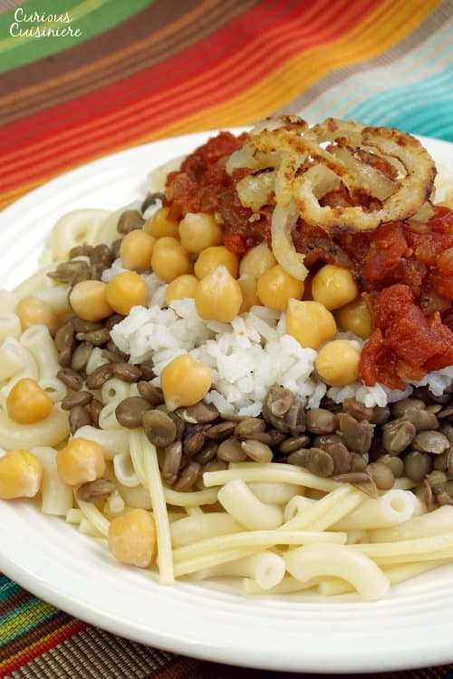 Often called the national dish of Egypt, Kushari is a hearty combination of flavors and textures all topped off with spicy tomato sauce and fried onions.   www.CuriousCuisiniere.com