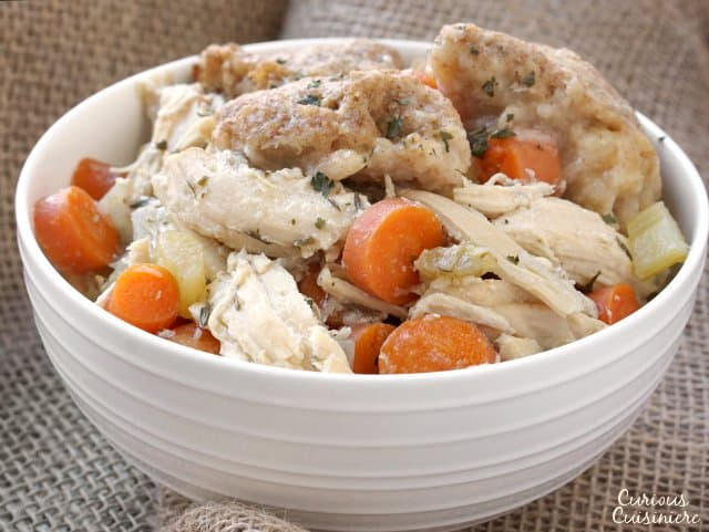 This Slow Cooker Chicken and Dumplings recipe is a hearty and slightly creamy stew made completely from scratch without canned cream of chicken soup!  | www.CuriousCuisiniere.com