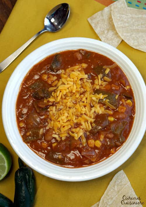 This slow cooker Vegetarian Enchilada Soup is packed full of flavorful peppers and hearty beans for a quick weeknight meal.   www.CuriousCuisiniere.com