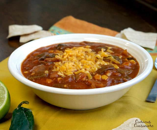 This slow cooker Vegetarian Enchilada Soup is packed full of flavorful peppers and hearty beans for a quick weeknight meal. | www.CuriousCuisiniere.com