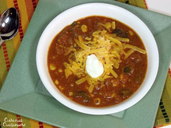 This slow cooker Cheesy Vegetarian Enchilada Soup is packed full of flavorful peppers and hearty beans for a quick weeknight meal.   www.curiouscuisiniere.com