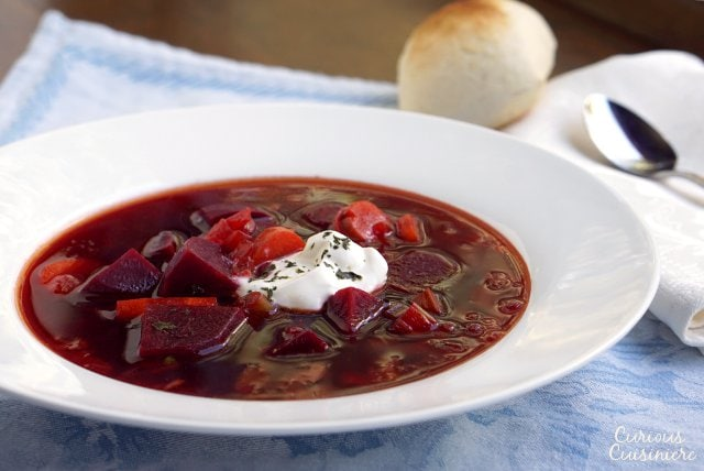 Our Polish Borscht recipe (Barszcz) creates a beet soup that is chock full of veggies and boasts a bright, sweet and sour flavor making it a perfect first course or warming meal. | www.CuriousCuisiniere.com
