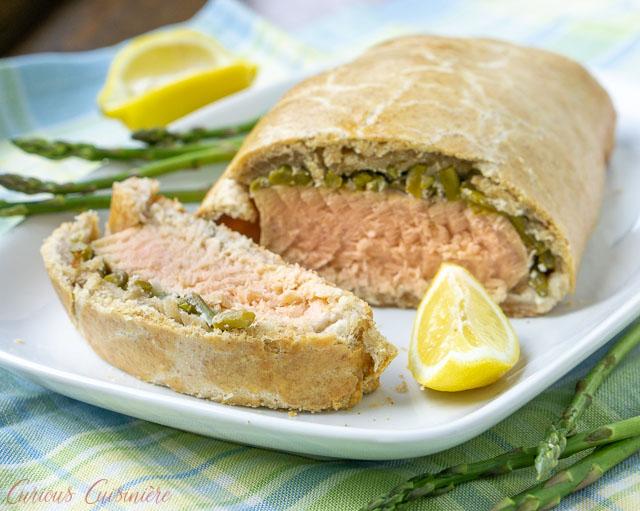 Salmon en croute with asparagus and cut lemons.