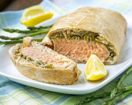 Lemon rosemary salmon en croute with asparagus on a white plate.