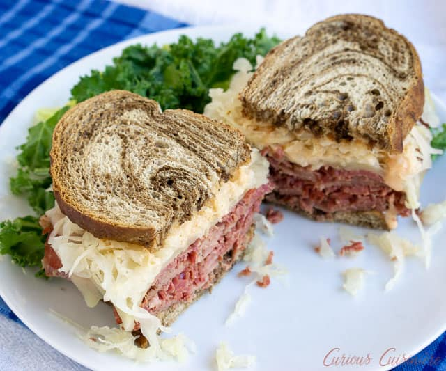 The classic grilled Reuben Sandwich is the perfect combination of crispy toast, flavorful corned beef, tangy sauerkraut, and creamy Russian dressing. | www.CuriousCuisiniere.com