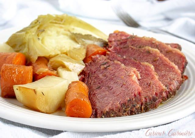 A plate of corned beef brisket with cabbage, potatoes, and carrots.
