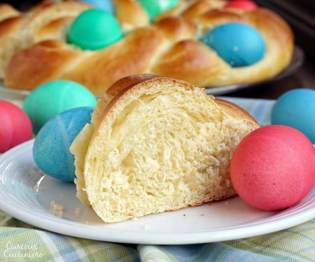 A slice of Italian Easter Bread, Pane di Pasqua, surrounded by dyed Easter eggs. | www.CuriousCuisiniere.com