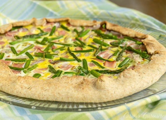 This Ham and Asparagus Tart is light and perfect for spring with strips of leftover ham and thin asparagus spears, roasted perfectly in a lemon herb crust. | www.CuriousCuisiniere.com