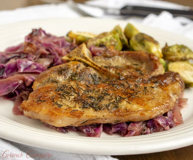 Bring a taste of fall to your dinner table with this German-inspired skillet recipe of apple cider pork chops with red cabbage. Everything is braised to tender, flavorful perfection! | www.CuriousCuisiniere.com