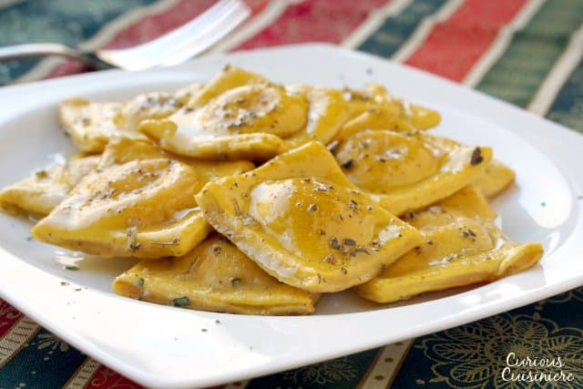 Pumpkin infused homemade pasta makes the perfect vessel for a creamy tarragon cheese filling in this fall Pumpkin Ravioli Recipe.  | www.CuriousCuisiniere.com