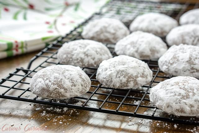 Powdered sugared German Pfeffernusse Spice Cookies on a baking rack wide shot