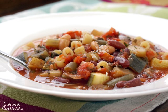 Our crock pot Minestrone is not a wimpy soup. Full of chunky vegetables and laden with herbs, this is some serious comfort food made easy in your slow cooker. | www.CuriousCuisiniere.com