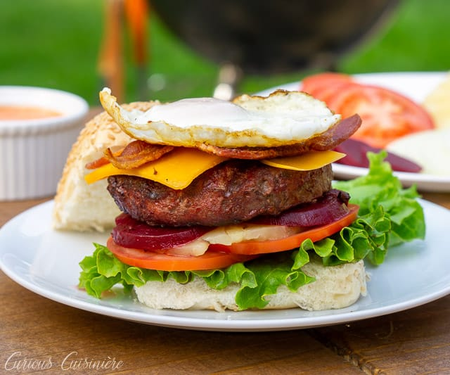 This loaded Australian Hamburger is a mile-high burger with egg, bacon, cheddar cheese, pineapple, pickled beets, sweet onion, lettuce, tomato, and a chili mayo sauce. If you love burger toppings, this Aussie Burger is for you! | www.CuriousCuisiniere.com