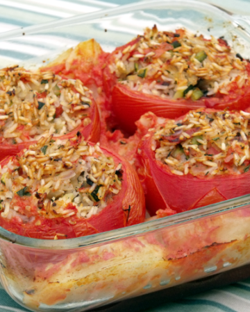 Big, juicy tomatoes stuffed with a healthy, vegetarian filling of rice, zucchini, and eggplant, surrounded by tomato infused roasted potatoes. A perfect summer meal!