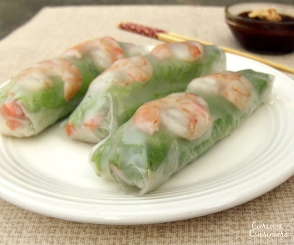 Pork, shrimp, lettuce, fresh herbs, carrots, and rice noodles are wrapped in rice paper, making spring rolls a healthy lunch or snack. Includes detailed instructions on how to wrap and roll a spring roll. | www.curiouscuisiniere.com