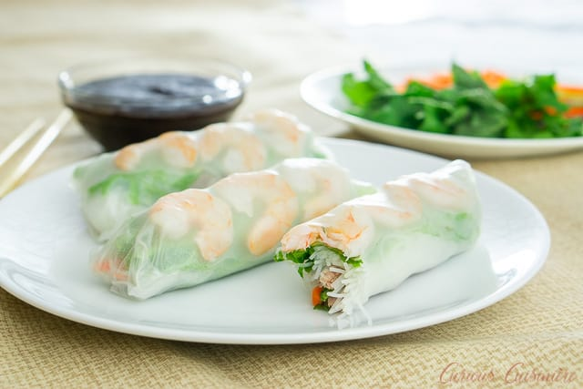Three Vietnamese fresh spring rolls with shrimp and greens on a white plate. With hoisin sauce for dipping.