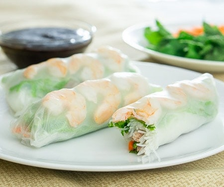 Three Vietnamese spring rolls with shrimp and greens on a white plate.
