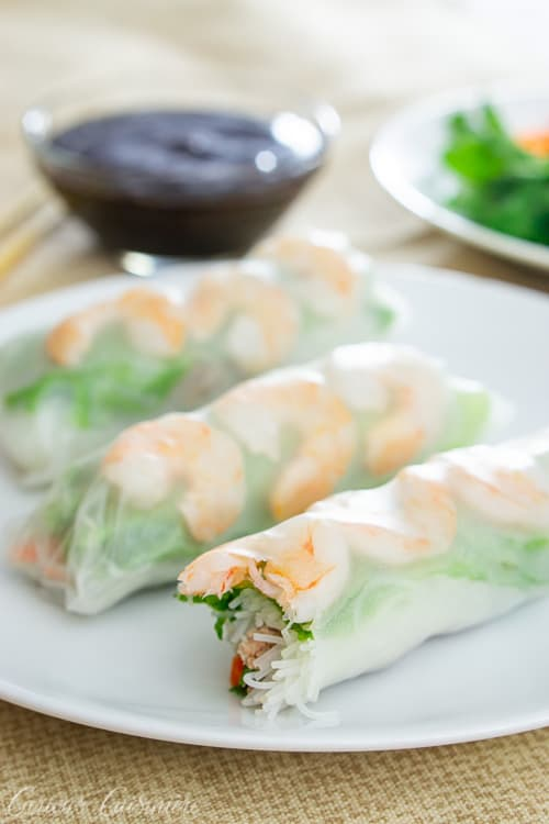 Three Vietnamese spring rolls with shrimp and greens on a white plate. With hoisin sauce for dipping.