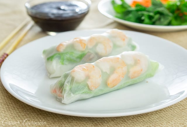 Two Vietnamese spring rolls with shrimp and greens on a white plate.