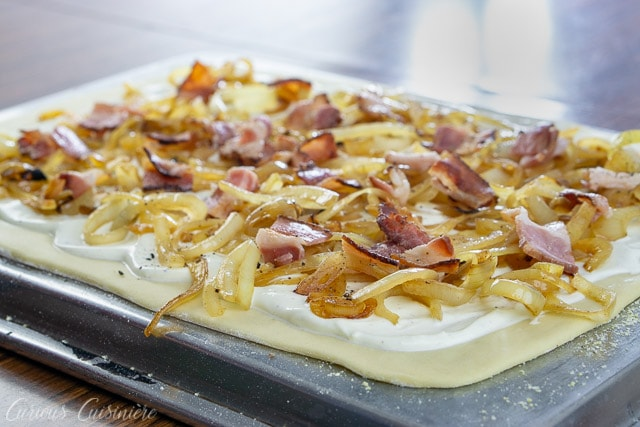 Layering bacon, caramelized onions, and creme fraiche on a thin crust for a classic German Flammkuchen recipe.