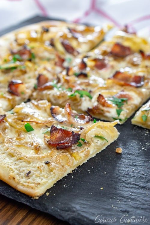 Bacon, caramelized onions, and a creamy base make up this classic German pizza, Flammkuchen, all on top of a cracker-thin, crispy crust.
