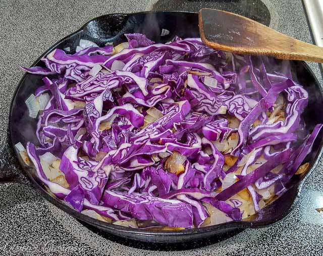 Making Blaukraut German braised red cabbage in a cast iron skillet.