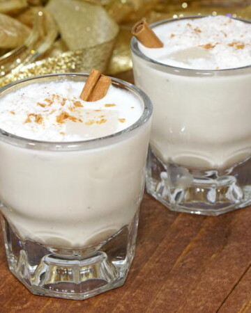 Rum and coconut milk give the Puerto Rican twist on eggnog a Caribbean flair. Smooth and creamy, this Coquito recipe is an easy drink to whip up for your holiday party guests! | www.curiouscuisiniere.com