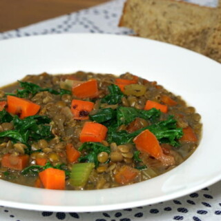 This hearty Lentil Soup with Kale is a Brazilian staple on New Year's Day when eating lentils provides good luck for prosperity in the coming year. | www.curiouscuisiniere.com