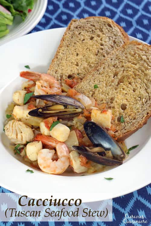 Cacciucco, a hearty Tuscan seafood stew, is served over toasted bread croutons for a fun and comforting meal. | www.CuriousCuisiniere.com