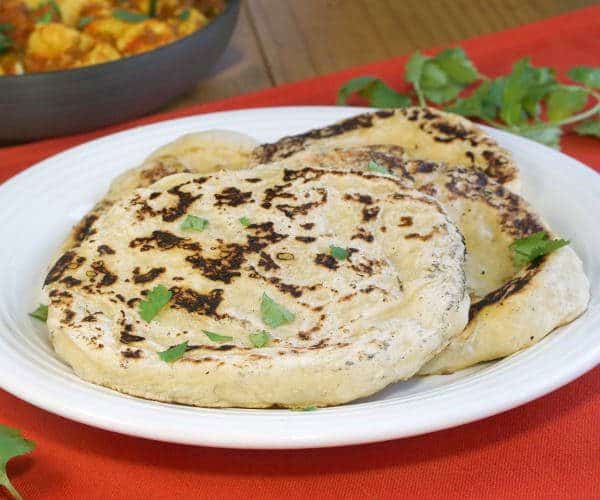 Our easy Naan recipe gives you perfectly textured, lightly charred, soft and chewy homemade Naan that is the perfect accompaniment to a saucy curry or lentil dal. | www.CuriousCuisiniere.com