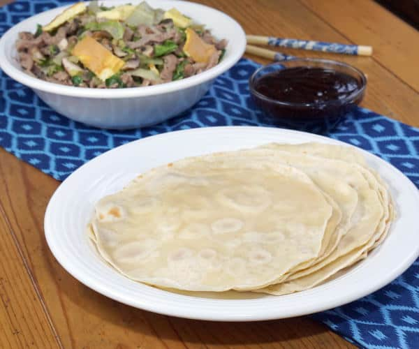 Paper thin Mandarin Pancakes are pleasantly chewy and incredibly light. These easy to make pancakes are perfect for filling with flavorful dishes like Moo Shu Pork and Peking Duck.   www.CuriousCuisiniere.com