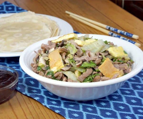 Moo Shu Pork is a traditional Chinese stir fry dish of pork, eggs, and mushrooms. This easy version comes together in a matter of minutes, making this recipe perfect for a weeknight dinner. | www.CuriousCuisiniere.com