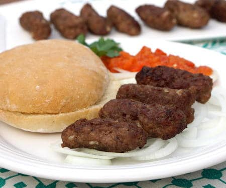 Cevapi are easy to make, grilled sausages from Southeastern Europe that burst with smoky flavor and are perfect for serving with flatbread and sliced onions. | www.CuriousCuisiniere.com