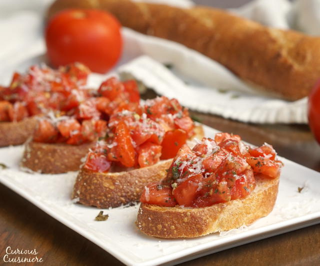 This recipe for a classic Tomato Basil Bruschetta features the perfect, bright and herby tomato topping served over crisp garlic toast. | www.CuriousCuisiniere.com